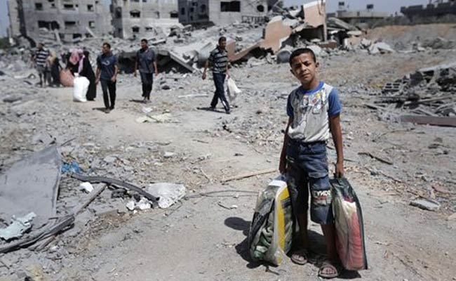 A Palestinian boy carries his belongings following heavy bombardment of Gaza by Israeli forces in August 2014 (Photo: Associated Press)