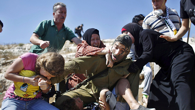 Ahed Tamini, also known as 'Shirley Temper,' biting the IDF soldier (Photo: Reuters)