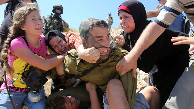 Members of the Tamimi family struggle with IDF soldier (Photo: AFP)